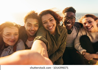 Cheerful friends taking selfie on a holiday. Group of men and women sitting outdoors on a summer day making self portrait.