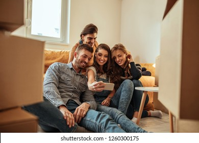 Cheerful friends taking selfie while moving into new home
