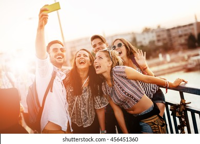 Cheerful friends taking selfies and smiling