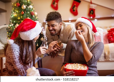 Cheerful friends telling jokes and having fun during Christmas.