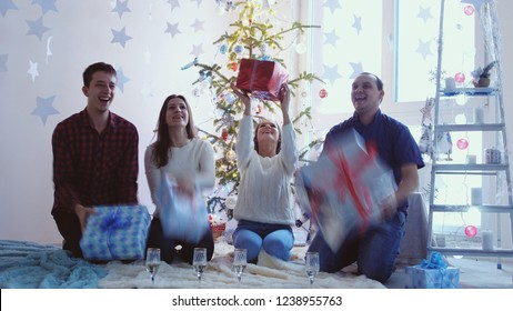 Cheerful friends throw and catch the boxes gifts. Presents fly into their hands. Cheerful friends celebrate Christmas.