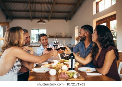 Cheerful friends toasting red wine at dinning table during dinner party. Group of men and women sitting around a dining table having wine.