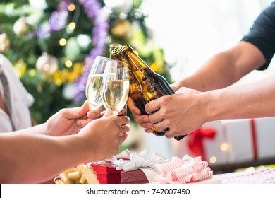 cheerful Friends toasting sparkling wine. Close-ups hands of two friends toasting wine glass in the dinner party for celebrating new year on the bokeh of light decorate on christmas tree background.