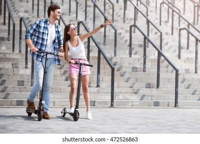Cheerful friends using scooter
