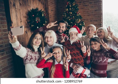 Cheerful full family showing two finger festure v-sign. Noel gathering. Cheerful grandparents grandchildren sister brother, son daughter taking self photo, photographing on mobile cell cellphone phone