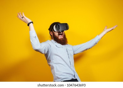 Cheerful funny bearded hipster man in casual having experience with VR glasses, goggles 3d view. Amazed bearded man with Virtual Reality gogles.