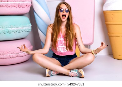 Cheerful funny girl sitting on the floor in lotus pose. Happy blonde woman in pink singlet and shorts smiling and making grimace face. Meditation and crazy emotions, pleasure.