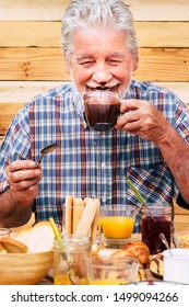 Cheerful and funny happy people old senior man drinking hot chocolate for breakfast at home or hotel -concept of nice elderly lifestyle for youth old caucasian male with young mind