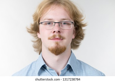 Cheerful funny looking nerdy guy with ginger hair and eyeglasses having beard.
