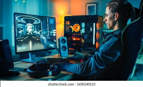 Cheerful Gamer Playing First-Person Shooter Online Video Game on His Powerful Personal Computer. Room and PC have Colorful Neon Led Lights. Cozy Evening at Home.