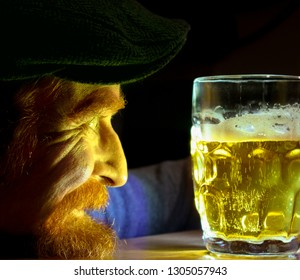 Cheerful ginger redhead man looking at mug with beer for St Patrick Day
