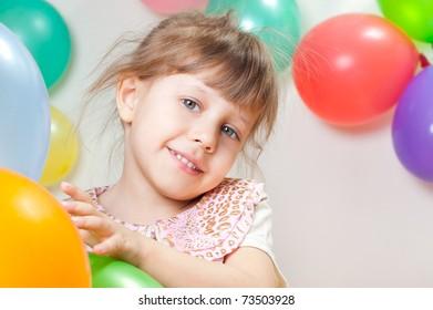Cheerful girl among the balloons