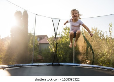Cheerful girl in backyard jumping on trampoline