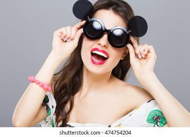 Cheerful girl in black round sunglasses with side glasses. Looking at camera, smiling widely. Touching glasses. Summer outfit, floral dress. Head and shoulders, studio, indoors