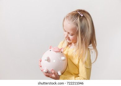 Cheerful girl with blond hair and piggy bank in the hands.