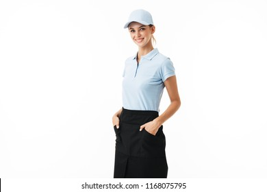 Cheerful girl in blue polo T-shirt and cap happily looking in camera holding hands in pockets over white background