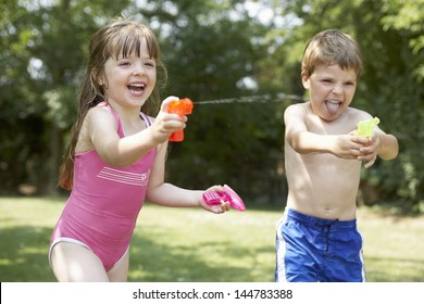 Cheerful girl and boy shooting water pistols in the backyard