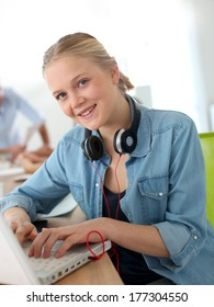 Cheerful girl in class working on laptop