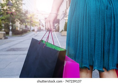 Cheerful girl doing shopping. Young woman carrying multi colored shopping bags while walking along the street. There's still more shopping to be done. Urban city woman