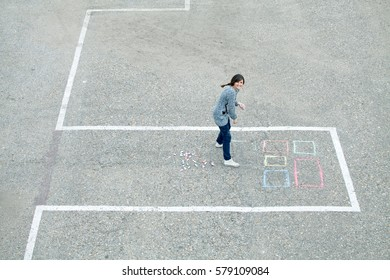 Cheerful girl draws chalk house / building