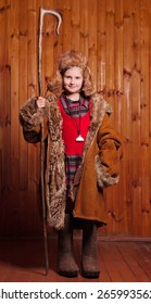 Cheerful girl dressed in a coat wearing boots and took the staff Shepherdess