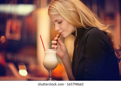 cheerful girl drinking coffee in a cafe at night
