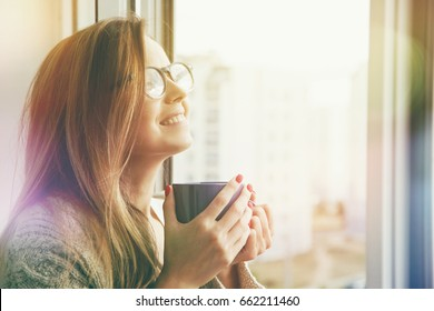 cheerful girl drinking coffee or tea in morning sunlight