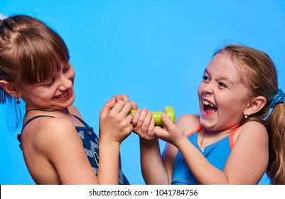 cheerful girl with dumbbells on blue background