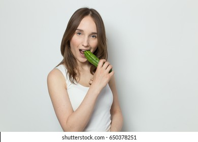 Cheerful girl eating cucumber on white background