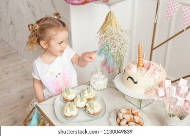 cheerful girl eats birthday cake, fun birthday with pretty little girl. Festive party with a unicorn.