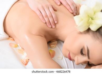 Cheerful girl enjoying massage at beauty salon