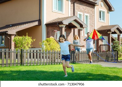 Cheerful girl flying kite with parents in the backyard