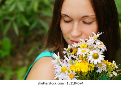 cheerful girl in the fresh air with a bouquet of daisies