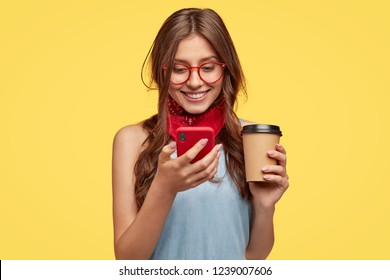 Cheerful girl has coffee break, rejoices buying new gadget, reads notification on red mobile phone, updates favourite app, types message and smiles at screen, wears glasses, isolated over yellow wall