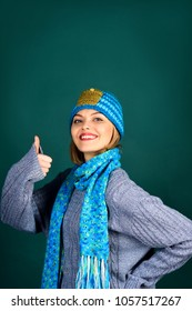 Cheerful girl in hat, scarf on neck, gray sweater shows thumb. Autumn/winter fashion, european style. Woman wears fashionable scarf, hat and sweater. Copy space from above for advertise clothing store