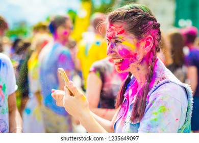Cheerful girl having fun at the holi color festival. Portrait of pretty smiling girl with multicolored face at the holiday of colors