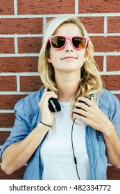 Cheerful girl with headphones posing outdoor