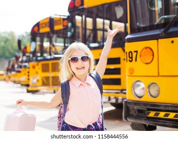 Cheerful girl with her hands up showing her excitement to go first time to school.