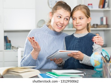 Cheerful girl and her young mother doing home task at home