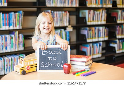 Cheerful girl holding the chalkboard with words- Back to school in the library