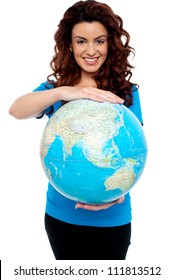 Cheerful girl holding globe safely with both hands. Holding from top and bottom.