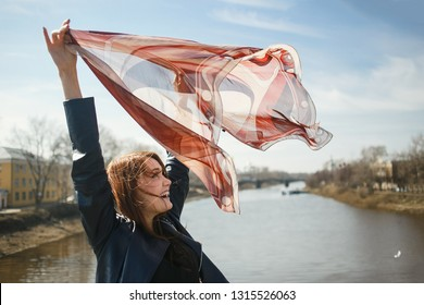 Cheerful girl holding a scarf, waving in the wind. Concept of spring, freedom, travel and windy weather.