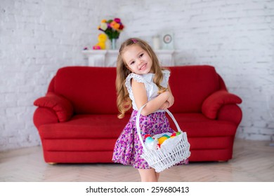 cheerful girl holding a white basket with colorful Easter eggs on red couch , the child laughs and fun