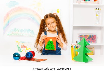 Cheerful girl holds orange card with Xmas tree