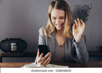 Cheerful girl in jacket making video call via smartphone. Young woman waving hand and smiling at phone screen. Video call concept