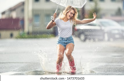 Cheerful girl jumping with white umbrella in dotted red galoshes. Hot summer day after the rain woman jumping and splashing in puddle