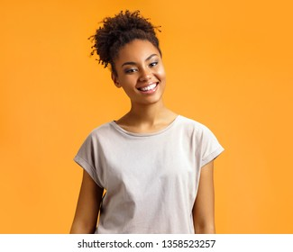 Cheerful girl laughs happily. Photo of african american girl wears casual outfit on orange background. Emotions and pleasant feelings concept.