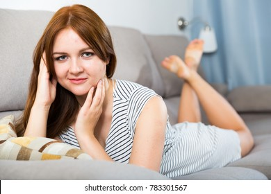 Cheerful girl is lying on sofa and playful posing at home.