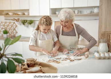 Cheerful girl is making shape of cookie with interest. Her granny is helping her while standing in kitchen