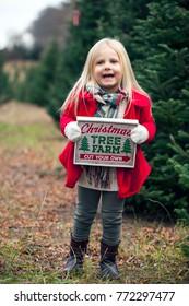 cheerful girl on fur tree farm before Christmas